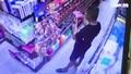 Người đàn ông áo đen bôi nước bọt lên hàng hóa trong một siêu thị