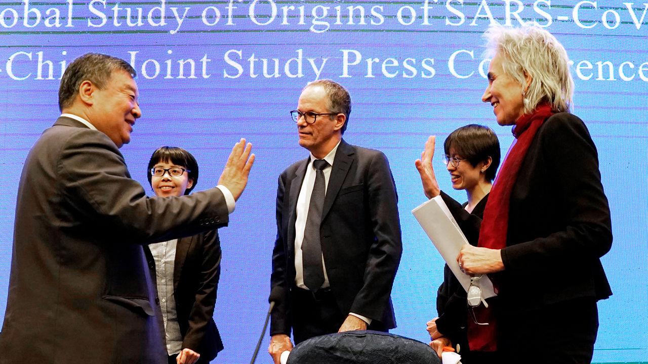 Peter Ben Embarek (giữa) and Marion Koopmans (bên phải) chào cộng sự Liang Wannian (trái) sau cuộc họp báo ngày 9/2 thông tin về việc điều tra nguồn gốc dịch bệnh COVID-19. Ảnh: AP