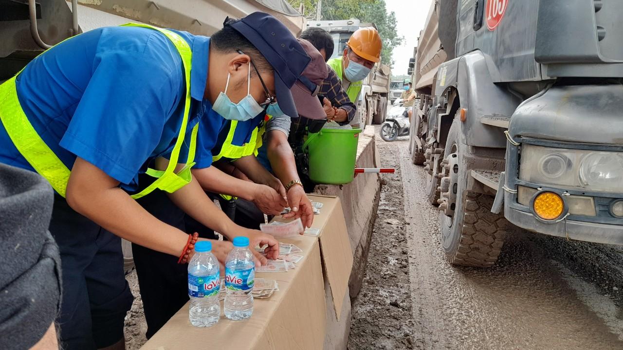 Hàng chục lái xe đồng loạt dùng tiền lẻ trả phí qua trạm vào mỏ đá Tân Cang