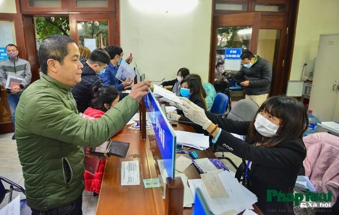 Cán bộ bộ phận một cửa Sở Tư pháp Hà Nội thường xuyên nhắc nhở và cấp khẩu trang cho người dân. Ảnh: PLXH
