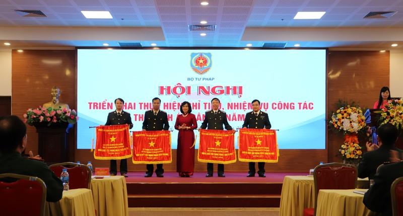 Thứ trưởng Bộ Tư pháp Đặng Hoàng Oanh trao Cờ Chính phủ cho Cục THADS Khánh Hoà (ngoài cùng bên phải), đơn vị xuất sắc trong phong trào thi đua 2018.