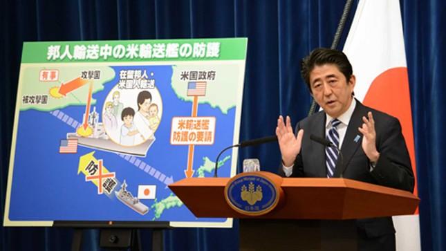 Ông Abe phát biểu trước bức tranh minh họa cảnh tàu Mỹ chở công dân Nhật bị tấn công - Ảnh: AFP