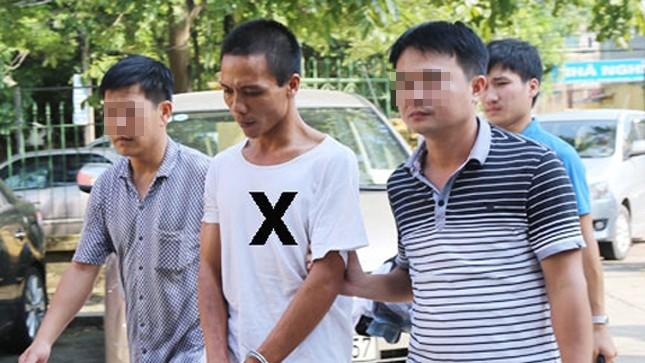 Thủ phạm Phan (áo trắng) được cảnh sát dẫn giải về trụ sở