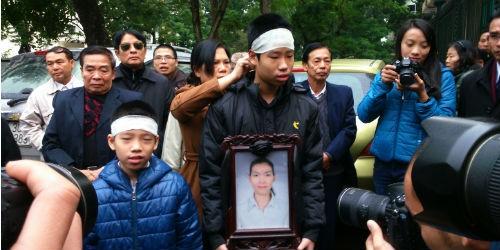Hai đứa con của chị Huyền ôm di ảnh dự tòa