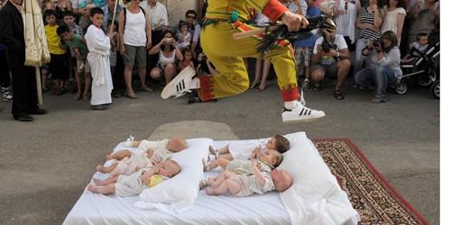 Một người đàn ông đại diện cho ma quỷ thực hiện nghi thức nhảy qua đầu trẻ em.
