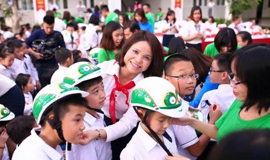 Bà Đỗ Thị Mai Hiệu trưởng trường tiểu học Dịch Vọng B - đội mũ bảo hiểm cho học sinh trong buổi lễ.