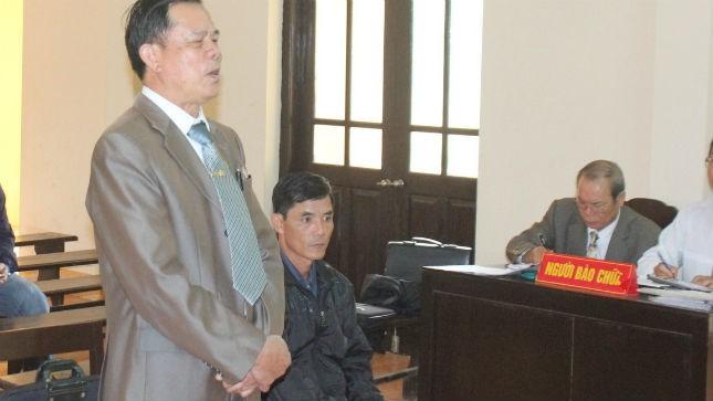 Ông Ngô Thanh Kỳ, Giám đốc Cty Cờ Đỏ (đứng) và ông Vũ Đình Đảng (ngồi) tại phiên tòa xét xử ngày 06/5/2014