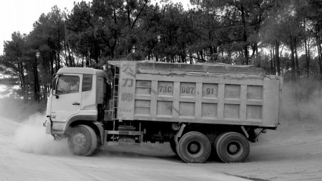 """Một xe """"khủng"""" đã được cơi nới thùng, chở đầy đất từ hướng mỏ đất xã Vĩnh Ninh về QL9B làm bụi đường tung lên mù mịt"""