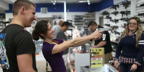 Một khách hàng nữ thử súng tại cửa hàng bán vũ khí ở Pompano Beach, Florida. (Ảnh: AFP)