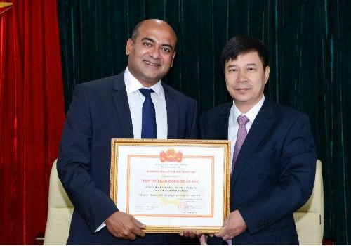 Đại diện lãnh đạo Vụ Thi đua - khen thưởng Ngân hàng Nhà nước (phải) trao tặng Danh hiệu Tập thể lao động xuất sắc cho Tổng giám đốc của Prudential Finance