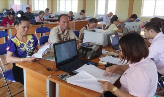 Tổ trưởng Tổ TKVV Cà Thị Nghĩa (ngoài cùng, bên trái) đến Điểm giao dịch của NHCSXH tại xã nộp lãi và tiết kiệm cho tổ viên