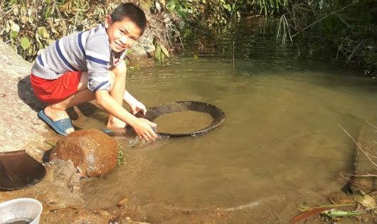 Trẻ con trong vùng nghỉ học cũng cầm theo mâm gỗ ra khe suối đãi quặng
