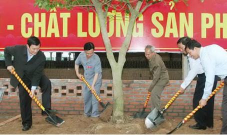 Cựu chiến binh Trần Thanh Hải (áo xám) cùng nguyên Chủ tịch nước Trương Tấn Sang, trồng cây lưu niệm tại Nhà máy gạch Nam Sơn. Ảnh: Hùng Minh