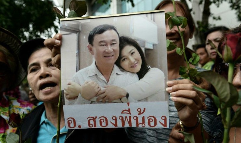 Người dân Thái Lan cầm ảnh bà Yingluck và anh trai