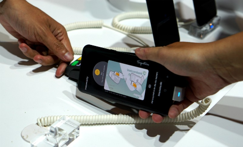 Chỉ cần chạm điện thoại vào máy POS là khách hàng đã có thể trả tiền thay vì lấy thẻ ra để quẹt