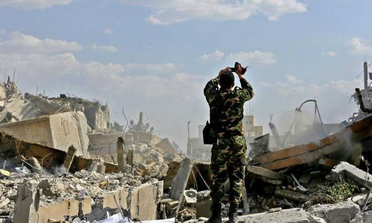 Một binh sỹ Syria kiểm tra một tòa nhà đổ nát sau cuộc không kích của Mỹ và các nước đồng minh
