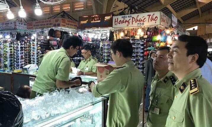 Ông Trần Hùng (bìa phải) cùng Tổ 334 kiểm tra xuất xứ hàng hoá tại chợ Bến Thành, TP HCM