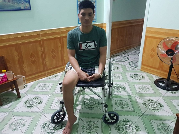 Anh Tú ngồi trên chiếc xe lăn với đôi chân không lành lặn