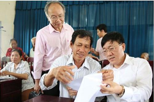 Tổng Giám đốc NHCSXH Dương Quyết Thắng (ngoài cùng bên phải) đang trao đổi với các Tổ trưởng tổ TKVV trong buổi làm việc tại Điểm giao dịch xã Tân Hạnh, huyện Long Hồ, tỉnh Vĩnh Long. Ảnh: Nguyễn Việt Hải