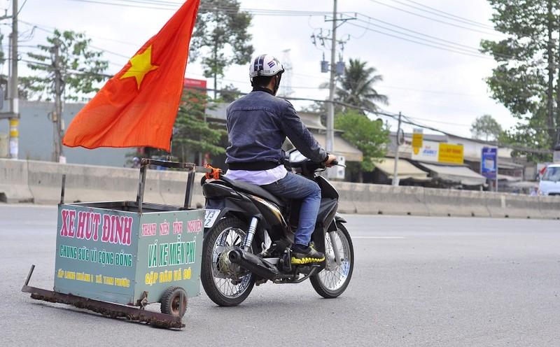 """Một người tình nguyện kéo xe có gắn nam châm để dọn đinh trên quốc lộ nhằm chống nạn """"đinh tặc"""""""