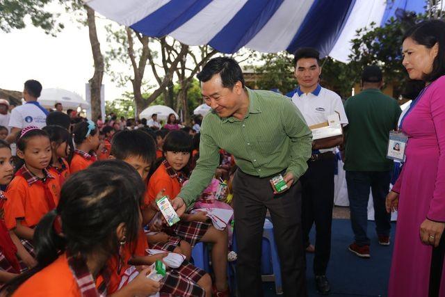 ông Đỗ Thanh Tuấn - Giám đốc Đối Ngoại Vinamilk trao sữa cho các em nhỏ