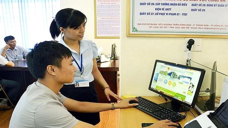 Cán bộ hộ tịch Hà Nội hướng dẫn người dân làm thủ tục đăng ký trực tuyến