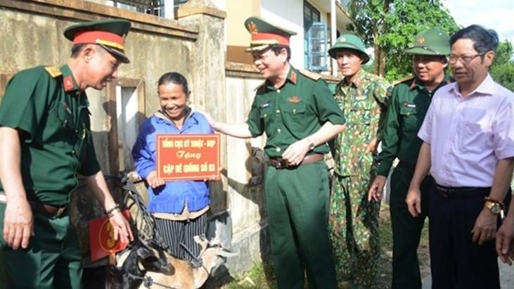 Thiếu tướng Nguyễn Văn Bình, Phó Chính ủy TCKT và lãnh đạo xã Hướng Hiệp, huyện Đa Krông trao dê giống tặng các gia đình người có công trên địa bàn. Ảnh Duy Thành