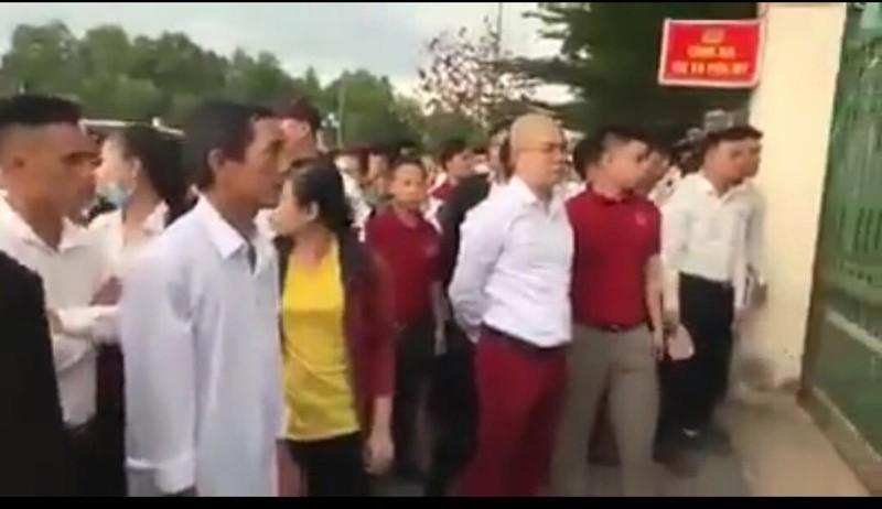 Ông Nguyễn Thái Luyện (áo trắng, quần đỏ) và nhóm người tụ tập đòi người trước trụ sở công an (ảnh cắt từ clip)