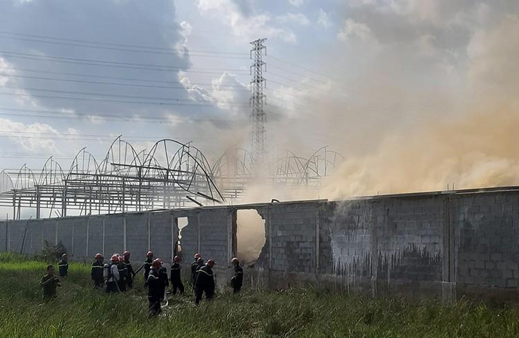 Cảnh sát đập tường tiếp cận đám cháy, dập lửa. Ảnh: Minh Tân.