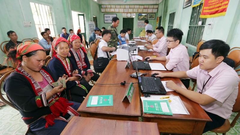 NHCSXH giải ngân trực tiếp vốn vay cho bà con tại Điểm giao dịch xã Ảnh: Trần Việt