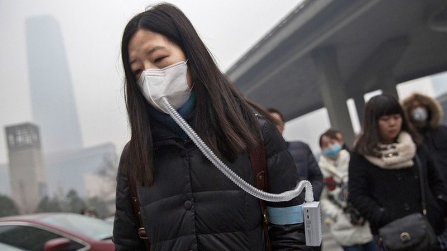 Bức ảnh về người phụ nữ sử dụng thiết bị lọc không khí tại Bắc Kinh là ví dụ về mức độ ô nhiễm tại thành phố này. (Nguồn: Internet)