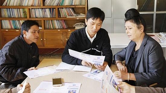 Nhân viên đại lý thu Bưu điện văn hóa xã Yên Hưng (Sông Mã) tuyên truyền chính sách BHXH tự nguyện cho người dân