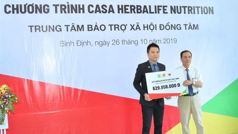 Ông Nguyễn Thành Đạt (trái) - Giám đốc Truyền thông Herbalife Việt Nam đại diện công ty trao tặng hơn 629 triệu đồng cho TTBTXH Đồng Tâm