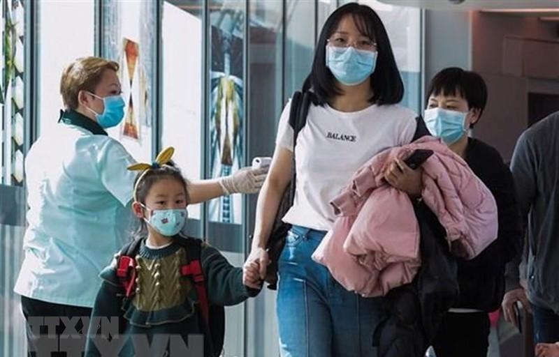 Nhân viên y tế Singapore theo dõi thân nhiệt hành khách qua máy quét tại sân bay quốc tế Changi ngày 22/1/2020. (Ảnh: AFP/TTXVN)