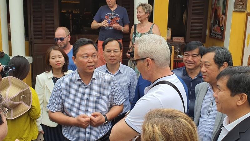 Chủ tịch tỉnh Quảng Nam Lê Trí Thanh (bên trái) xuống đường trò chuyện với du khách ngày 22/2