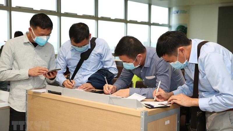 Nhân viên y tế kiểm tra phiếu khai báo y tế của hành khách trước khi làm thủ tục nhập cảnh tại cửa khẩu Nội Bài chiều 7/3.  (Hình: Dương Giang/TTXVN)