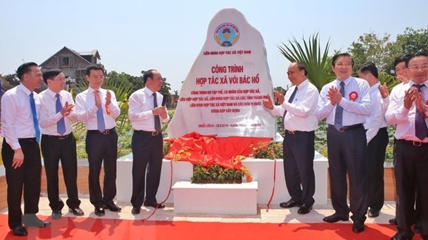 Thủ tướng Chính Phủ Nguyễn Xuân Phúc cùng các lãnh đạo gắn biển Công trình 'Hợp tác xã với Bác Hồ.' (Ảnh: Danh Lam/TTXVN)