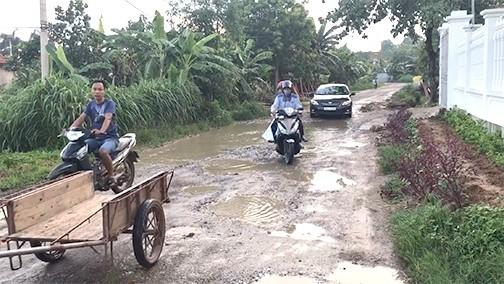 Người dân địa phương vất vả đi qua tuyến đường.