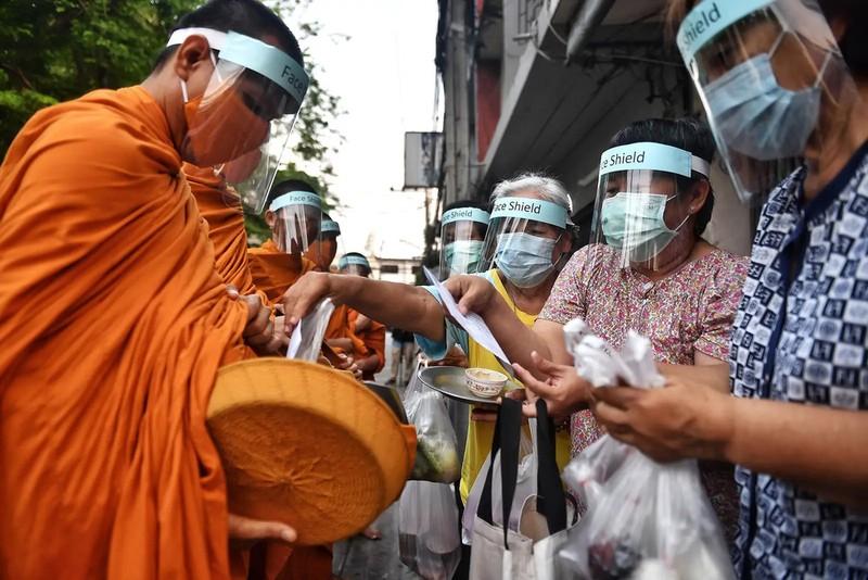 Các nhà sư của chùa Wat Matchantikaram đeo mặt nạ che mặt khi đi cầu thực trên đường phố Bangkok, Thái Lan ngày 31-3-2020 - Ảnh GETTY IMAGES.
