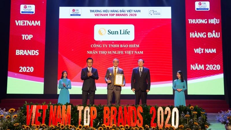 Ông Larry Madge - Tổng Giám đốc Sun Life Việt Nam (đứng giữa) nhận danh hiệu Top 10 Thương hiệu hàng đầu Việt Nam từ Ban tổ chức.