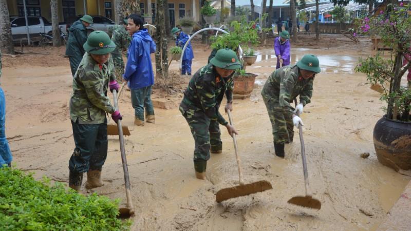 Cán bộ, nhân viên Đoàn KT-QP 337 giúp dân dọn bùn sau mưa lũ.