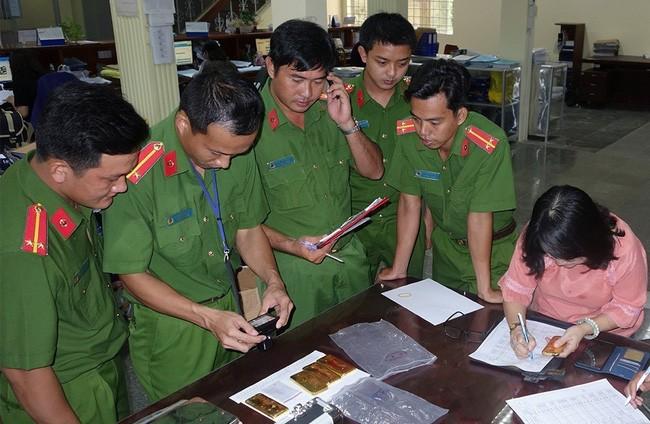 Lực lượng chức năng kiểm tra trọng lượng số vàng thu giữ (Ảnh: TTXVN)