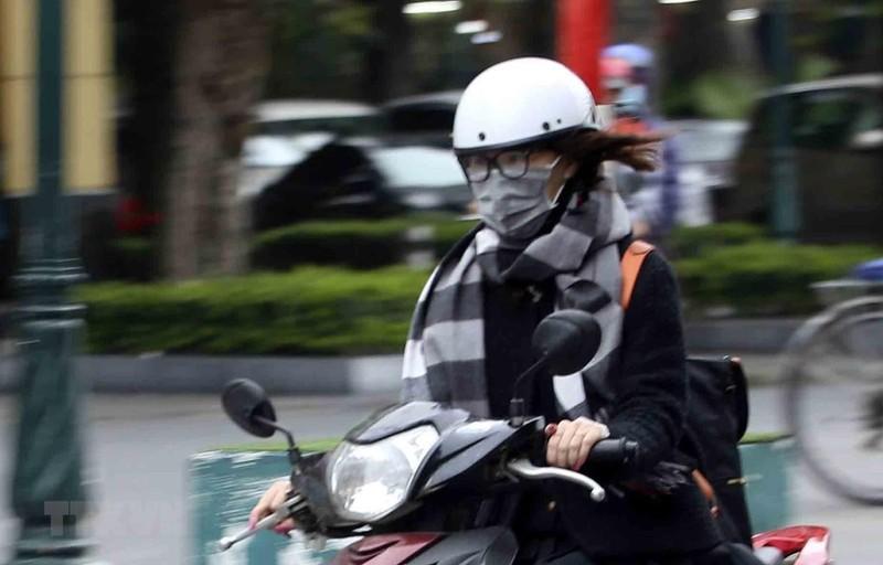 Giữ ấm cơ thể với nhiều lớp áo, khăn quàng và đeo khẩu trang khi ra đường khi trời rét đậm, rét hại. (Ảnh: Tuấn Đức/TTXVN)