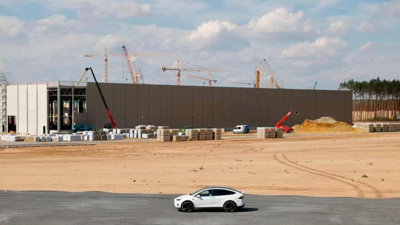 Elon Musk thị sát công trình xây dựng siêu nhà máy trên một chiếc xe điện Tesla © The Guardian.