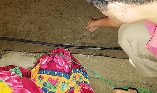 Người dân sử dụng bút thử điện kiểm tra đường dây điện dưới chân có điện chạy qua.