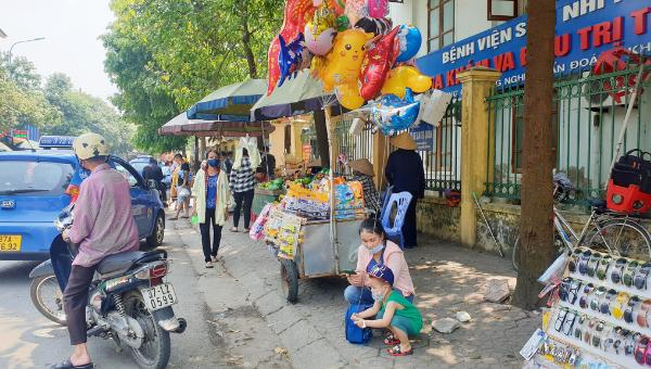 Vỉa hè bị chiếm dụng làm nơi buôn bán khiến người đi bộ phải đi dưới lòng đường.