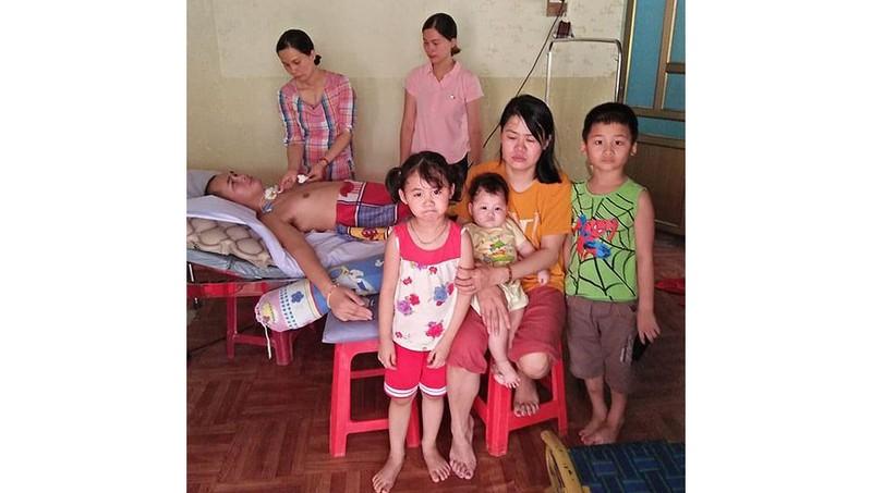 Chị Hà và 3 con nhỏ, bên người em chồng bị tai nạn lao động.