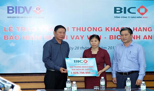 Tổng Giám đốc BIC Trần Hoài An (ngoài cùng bên trái) trao hơn 2 tỷ đồng tiền bảo hiểm BIC Bình An cho đại diện gia đình khách hàng Chu Thanh Phương (giữa)