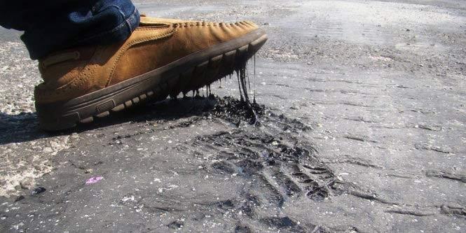 Nhựa đường chảy vì nắng nóng dính chặt vào giày người đi đường - Ảnh: Văn Định