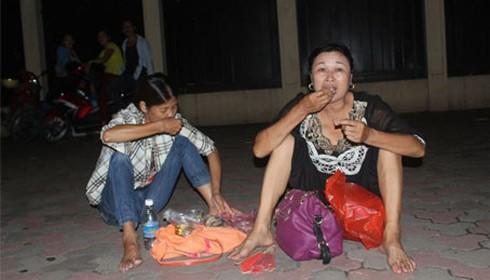 Bà Nghĩa (bìa phải) từ Hải Phòng lên Hà Nội, đang ngồi ăn cơm nắm trên vỉa hè